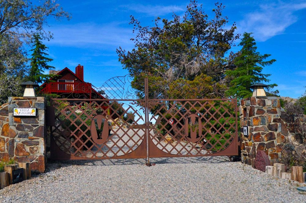 A look at the property's main entry featuring its gate and stone fence. Image courtesy of Toptenrealestatedeals.com.