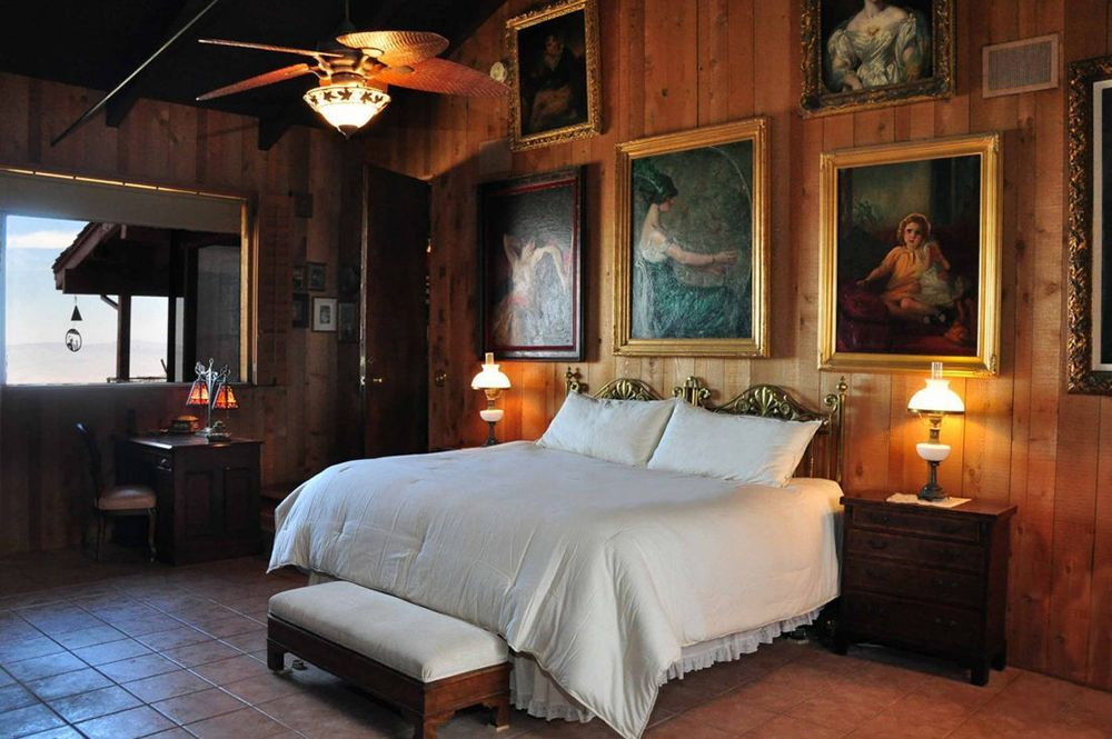This bedroom has multiple stunning and artistic wall decor paintings on its brown walls. Image courtesy of Toptenrealestatedeals.com.