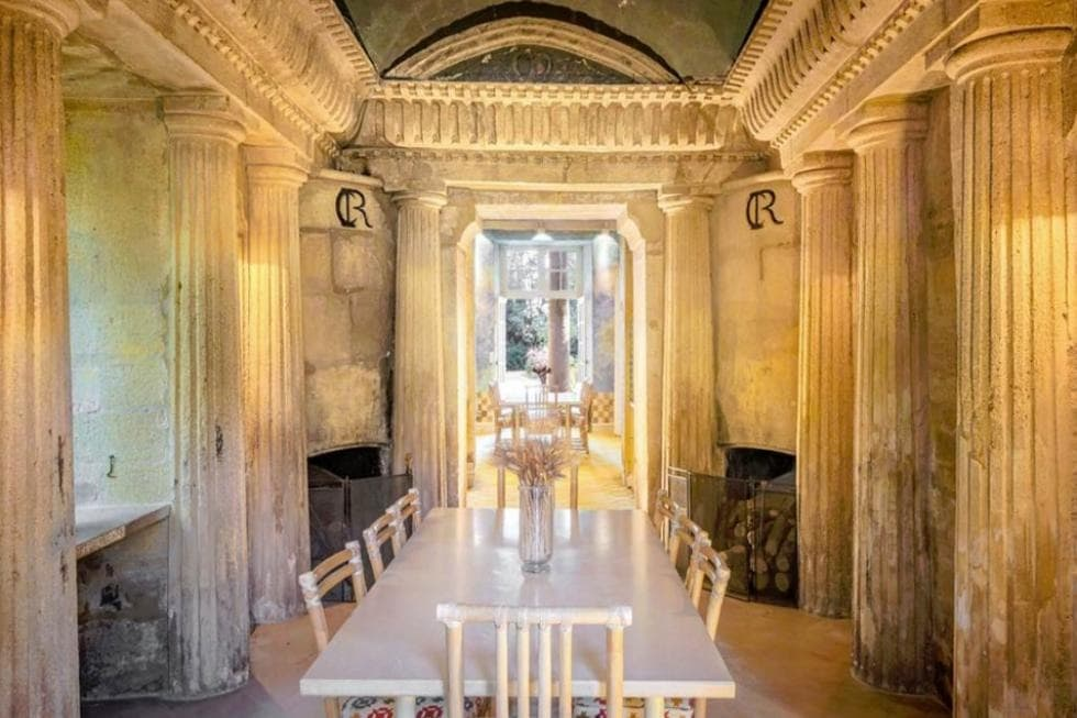 This is the formal dining room with a large white dining table surrounded by chairs that blend well with the walls adorned by tall pillars. These are all then topped with a tall cove ceiling. Image courtesy of Toptenrealestatedeals.com.