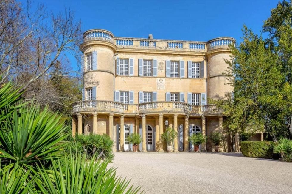 This is the front view of the house with a sandy beige tone to its exterior walls adorned with Greek-style pillars on the ground level adorned with green landscaping filled with potted plants, shrubs and tall trees. Image courtesy of Toptenrealestatedeals.com.