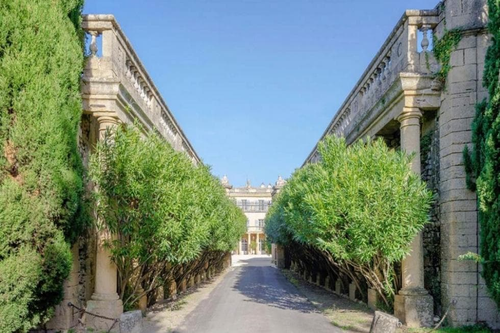 There is an area within property grounds with a wide walkway lined on both sides by trees placed in between the Greek pillars. This gives a unique aesthetic to the area as well as complement the exteriors of the house. Image courtesy of Toptenrealestatedeals.com.