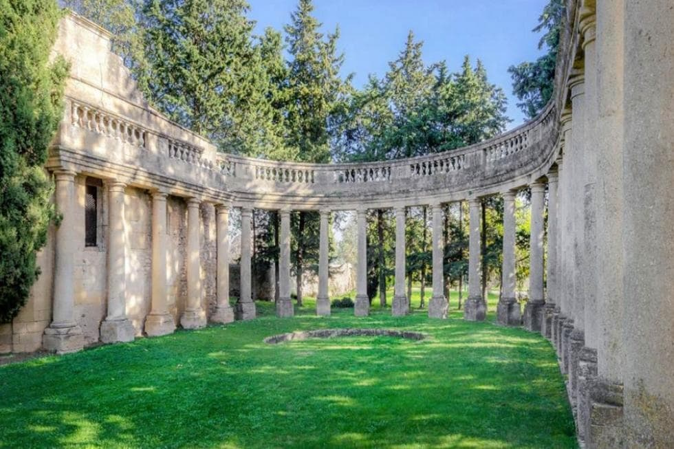 This is a grass lawn within the property that is surrounded by tall Greek-style pillars topped with tall trees. Image courtesy of Toptenrealestatedeals.com.