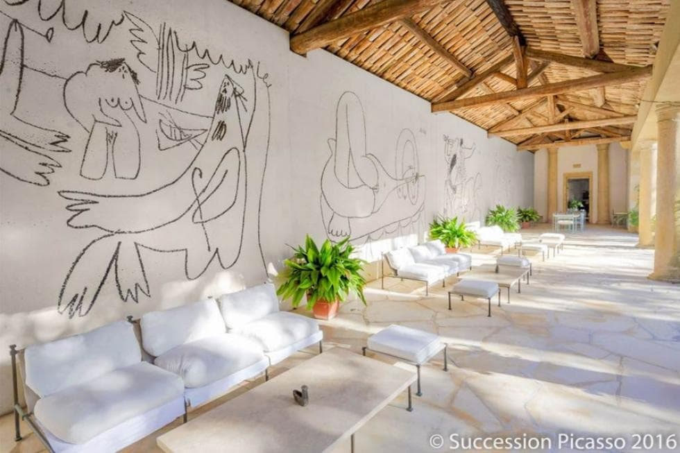 This is the large covered patio at the side of the house with a massive white wall adorned by the murals of Picasso. This gives a nice background for the cushioned sofas and large coffee tables that blend with the beige floor of the area that is topped with a wooden ceiling. Image courtesy of Toptenrealestatedeals.com.