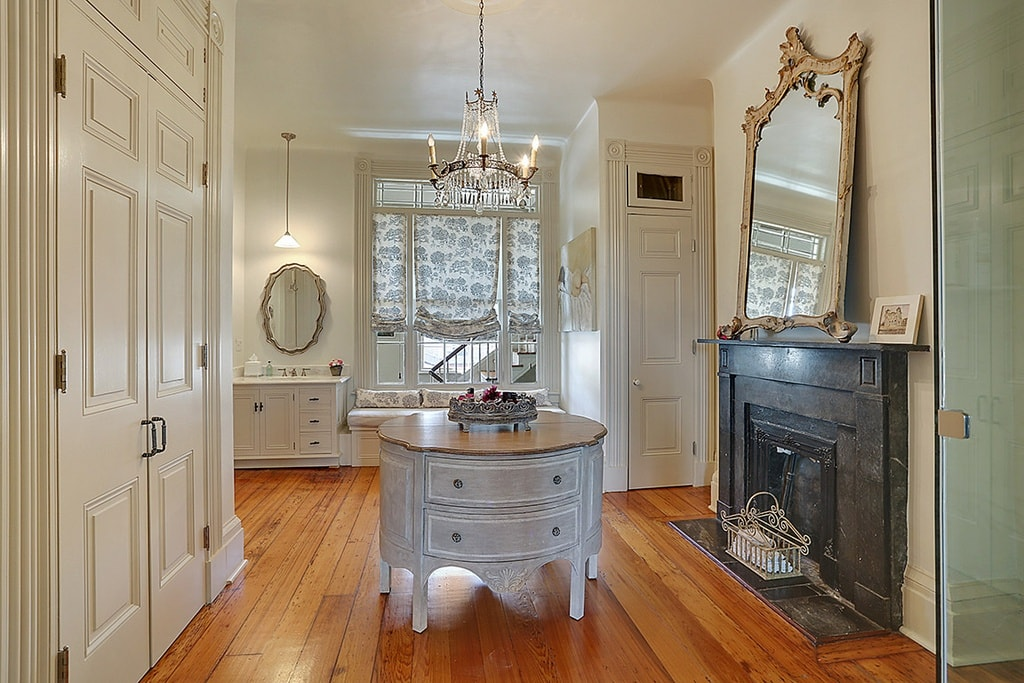 This is a spacious primary bathroom with an attached closet. These are warmed by the fireplace on the side with a black mantle that is topped with a wall-mounted mirror. Image courtesy of Toptenrealestatedeals.com.