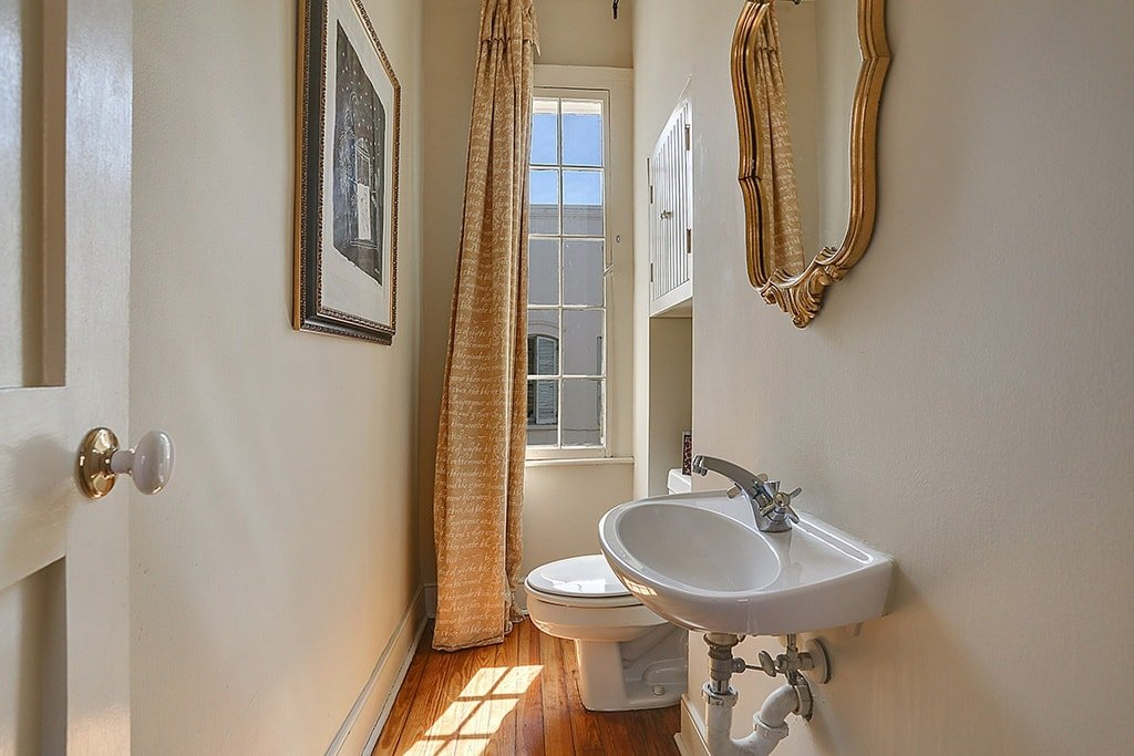 This is a tall and narrow bathroom with a toilet at the far end by the tall and thin window. Image courtesy of Toptenrealestatedeals.com.