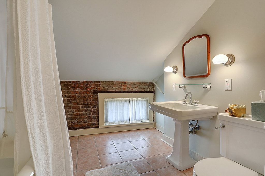 This simple bathroom has a low shed ceiling that gives a unique embrace to the ceramic pedestal sink and the toilet beside it. Image courtesy of Toptenrealestatedeals.com.