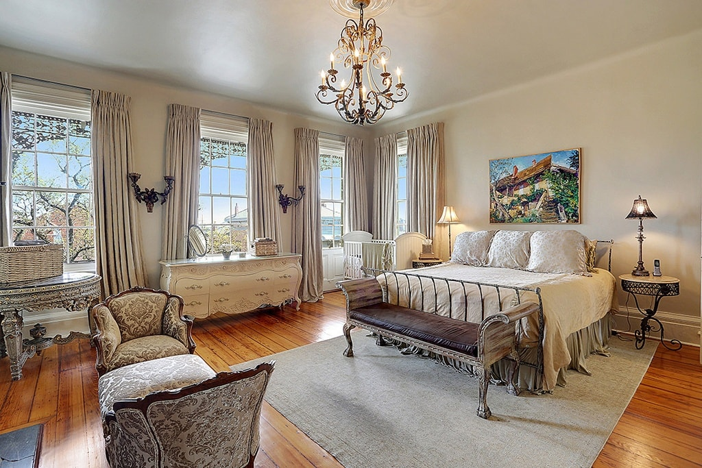 The primary bedroom has consistent beige walls and ceiling that match with the bed and the dresser. These are then contrasted by the chandelier that matches with the wall-mounted lamps in between windows. Image courtesy of Toptenrealestatedeals.com.