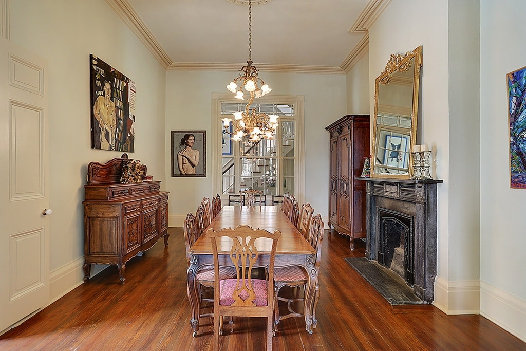 The formal dining room has a hardwood flooring that matches well with the wooden dining table. This is surrounded by wooden chairs and topped with a couple of small chandeliers. Image courtesy of Toptenrealestatedeals.com.