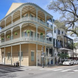 This is the front view of the mansion from the vantage of the street. Here you can see its light beige exterior walls adorned with two wrap-around balconies supported by thin pillars. Image courtesy of Toptenrealestatedeals.com.