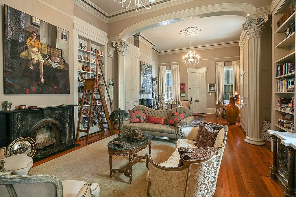 This is a close look at the library and its fireplace paired with comfortable sofas for reading nooks. The walls of this room has built-in bookshelves that reaches high to the ceiling. Image courtesy of Toptenrealestatedeals.com.