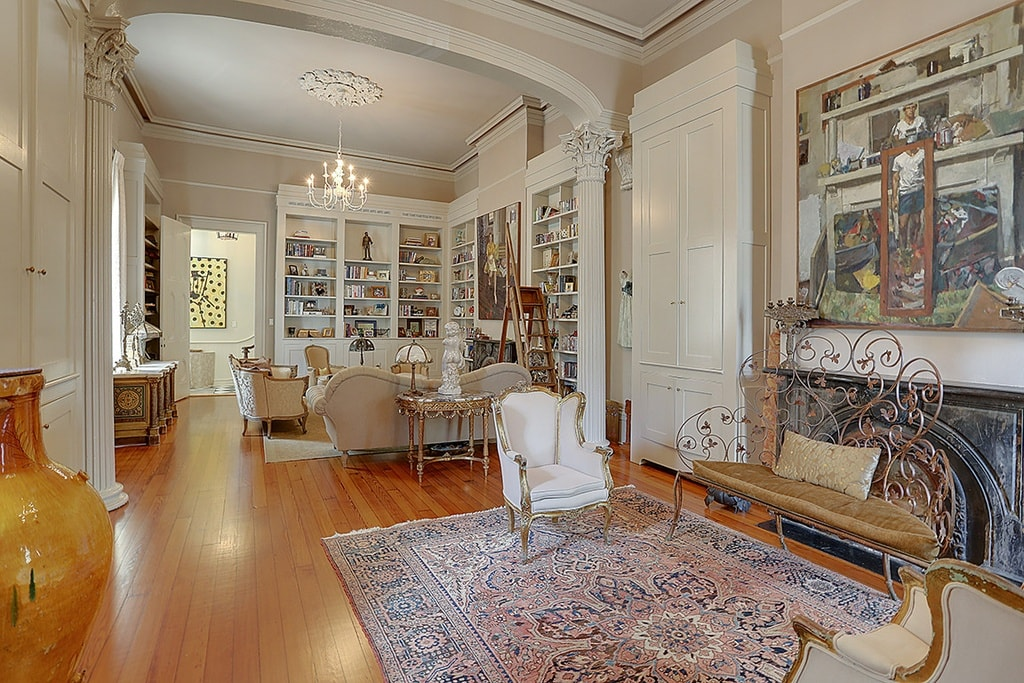 Here you can see the library at the far side. This area has its own fireplace paired with chairs on a patterned area rug that covers most of the hardwood flooring. Image courtesy of Toptenrealestatedeals.com.