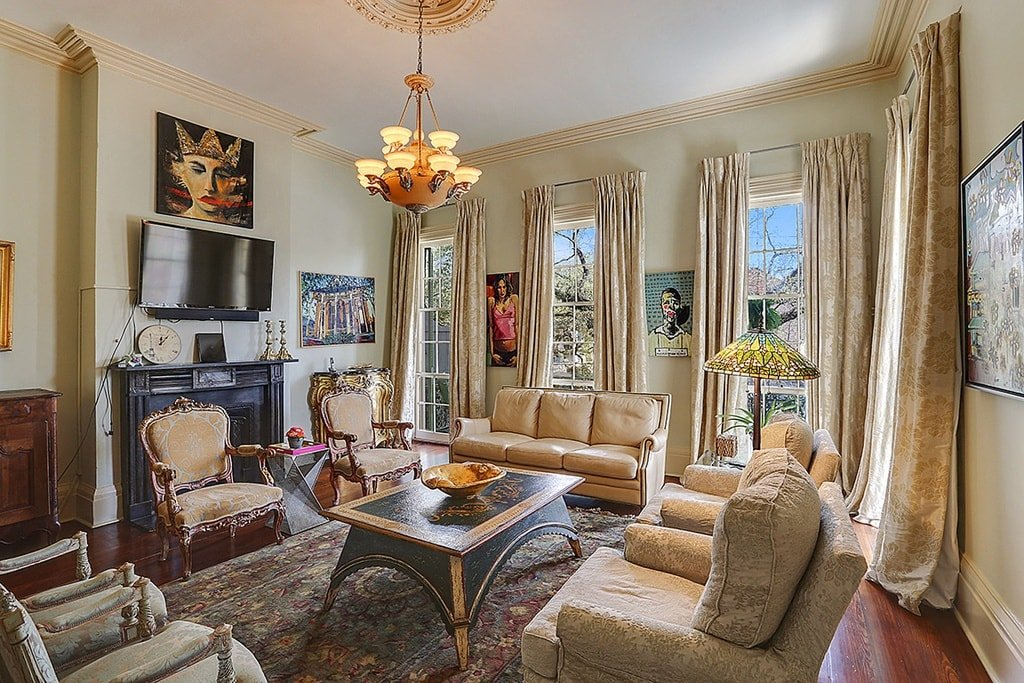 This is view of the living room shows the fireplace behind the two cushioned armchairs that is topped with a wall-mounted TV and an artwork above it. Image courtesy of Toptenrealestatedeals.com.