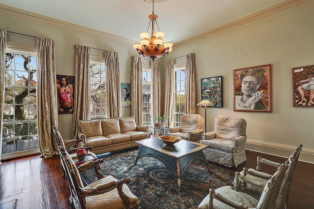This is the living room that has a beige sofa set surrounding a black wooden coffee table in the middle of the patterned area rug topped with a small chandelier. Image courtesy of Toptenrealestatedeals.com.