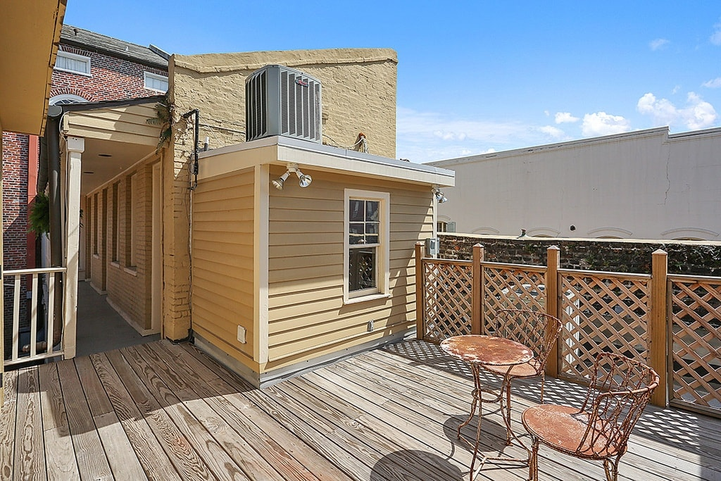 This is the rooftop deck of the mansion with wooden flooring that has a simple outdoor furniture and lines with wooden railings on the side. Image courtesy of Toptenrealestatedeals.com.