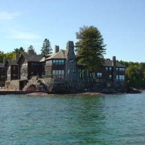 This is a view of the hunting lodge from the vantage of the lake. Here you can appreciate the size of the complex with dark brown tones to its exteriors that make the glass walls stand out. These are then complemented by the tall stone chimneys along with tall trees. Image courtesy of Toptenrealestatedeals.com.