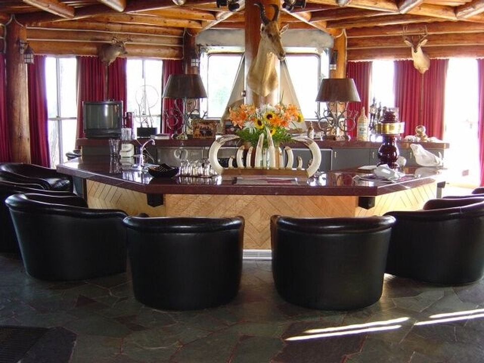 This is the circular bar with a dark countertop surrounded by dark leather chairs and topped with a wooden ceiling that has exposed beams. Image courtesy of Toptenrealestatedeals.com.