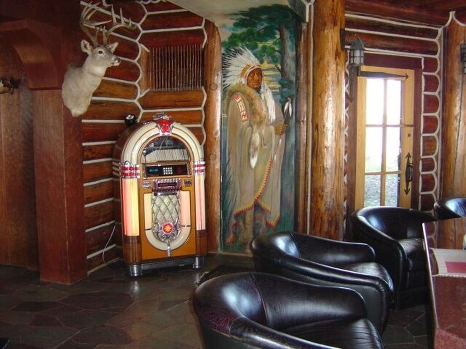 At the corner behind the dark leather chairs is a vintage jukebox adorned with a mural and a hunting trophy. Image courtesy of Toptenrealestatedeals.com.