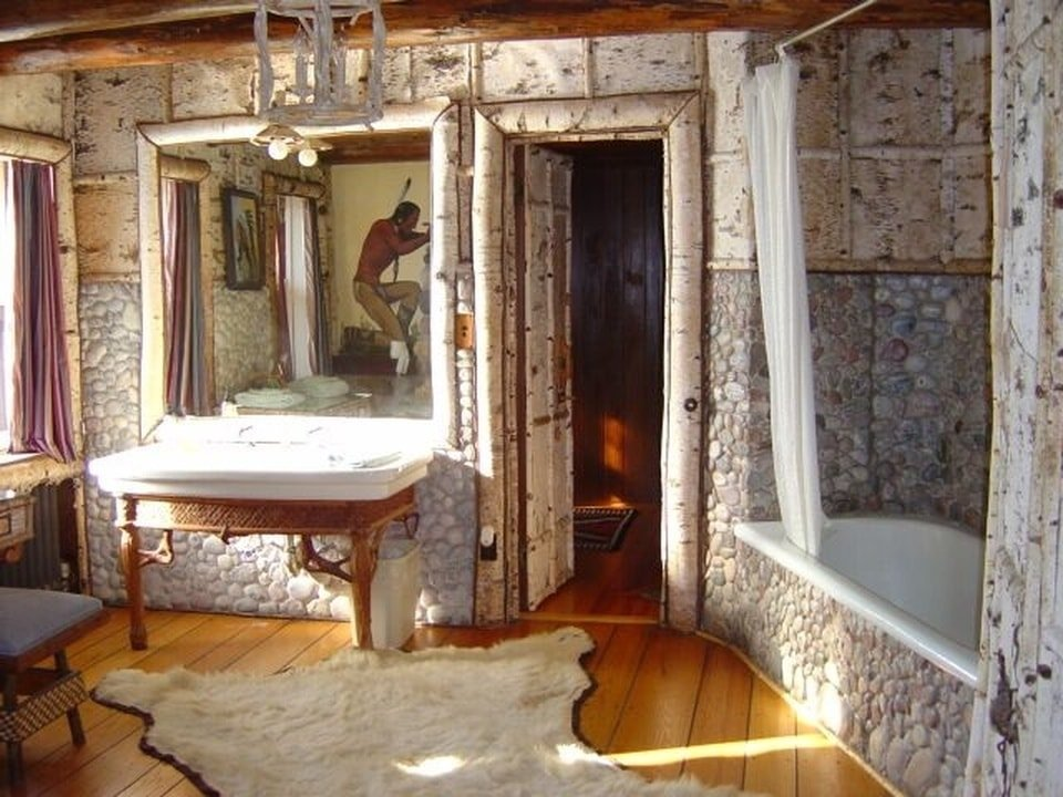 The bathroom has walls of small mosaic stones. It complements the large sink with a wooden support and the bathtub with a white shower curtain. Image courtesy of Toptenrealestatedeals.com.