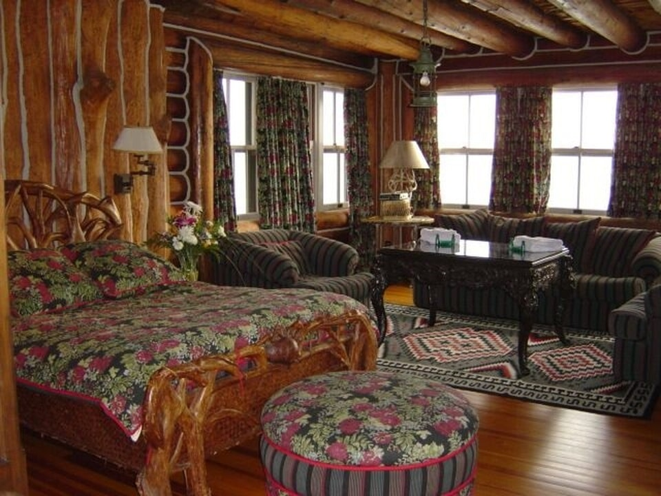 This bedroom has a rustic wooden bed adorned by the floral colorful sheets that match with the cushioned ottoman at it foot. On the side is a sitting area by the windows. Image courtesy of Toptenrealestatedeals.com.