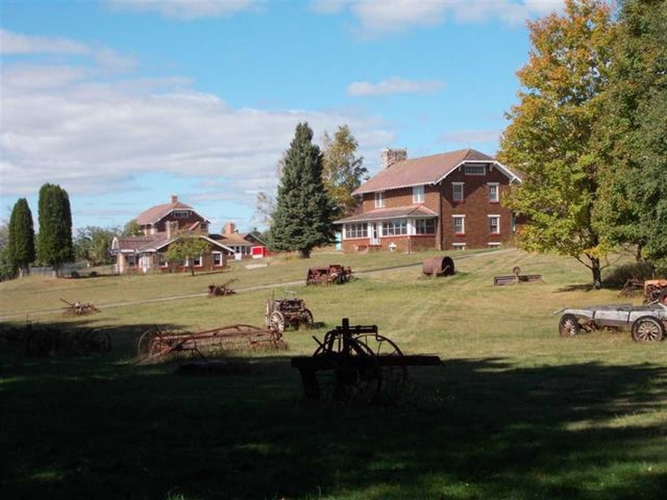The farm section of the property has wide and spacious open lawns of grass and rustic wooden structures that are complemented by the tall trees. Image courtesy of Toptenrealestatedeals.com.