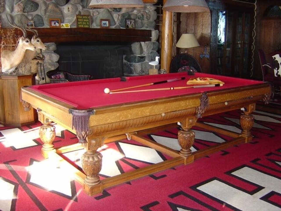 The game room has a large wooden pool table with a red surface to match the red carpeting of the floor. These are then warmed by the large stone fireplace on the side. Image courtesy of Toptenrealestatedeals.com.