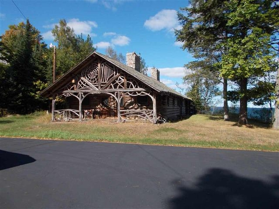 This is one of the buildings of the property facing the lake shore. It has a rustic look to its wooden accents and tall stone chimneys. Image courtesy of Toptenrealestatedeals.com.