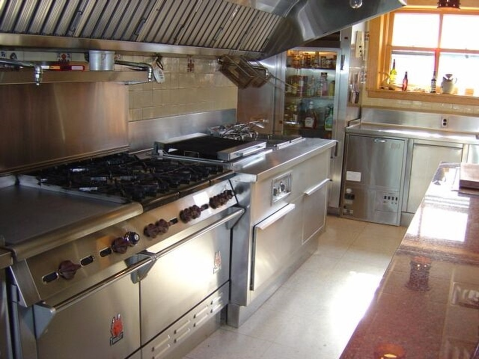 This side of the kitchen shows the stainless steel cooking area topped with a stainless steel vent. Image courtesy of Toptenrealestatedeals.com.