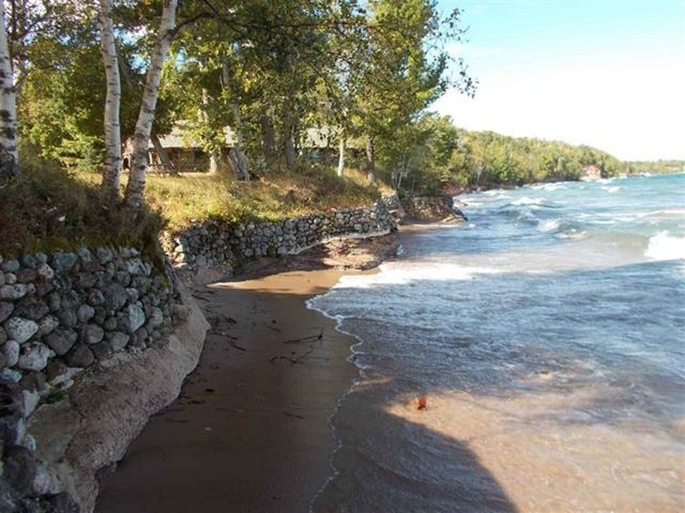 This is a close look at the lake shore of the property. You can see here that the land is bordered with mosaic stone walls lined with tall trees. Image courtesy of Toptenrealestatedeals.com.