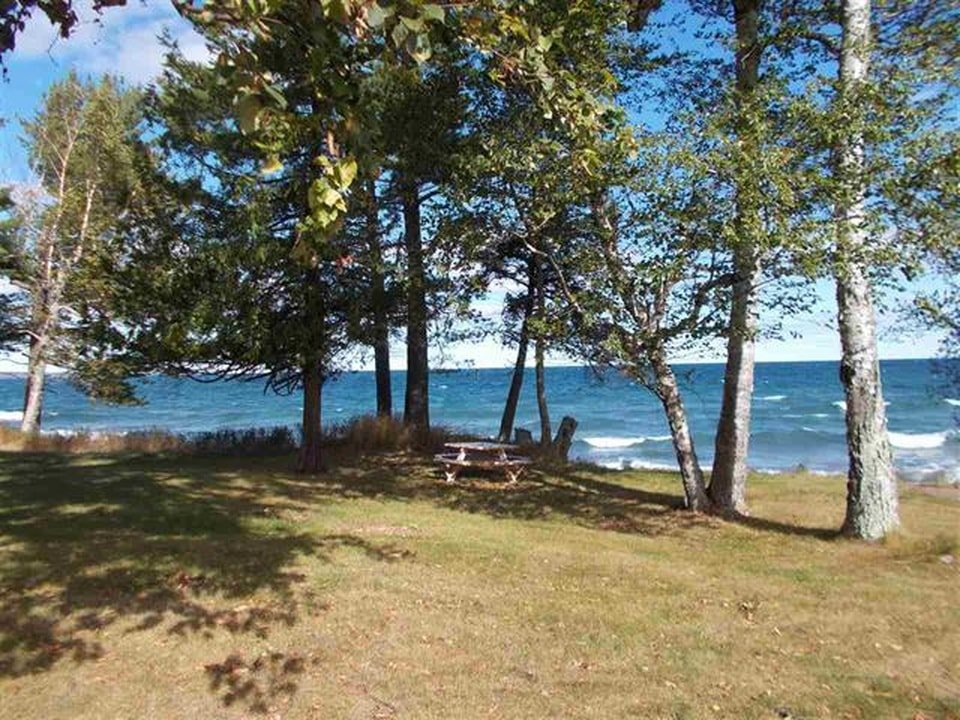 There is an area by the lake shore with tall trees that give shade to the rustic wooden outdoor picnic table with great view of the lake. Image courtesy of Toptenrealestatedeals.com.
