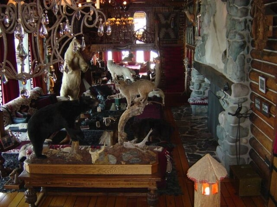 The living room has a large stone fireplace that brings warmth to the sofa set across from it. This area is also adorned with various hunting trophies. Image courtesy of Toptenrealestatedeals.com.