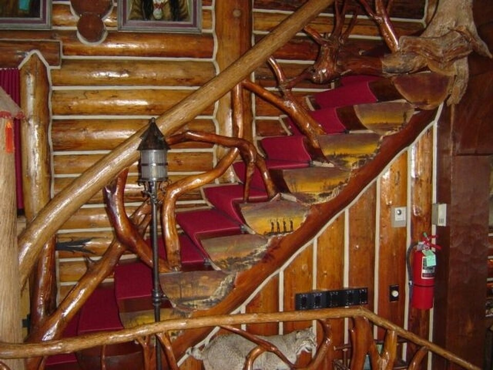 This is a close look at the wooden staircase of the lodge. Here you can see the rustic wooden railings contrasted by the red carpeting of the steps. Image courtesy of Toptenrealestatedeals.com.