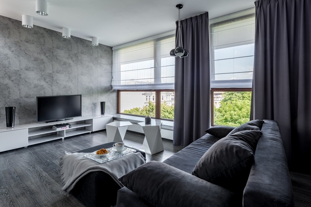This is a family room that has a gray wall to match with the dark gray flooring and sofa that are all illuminated by the natural light of the windows.