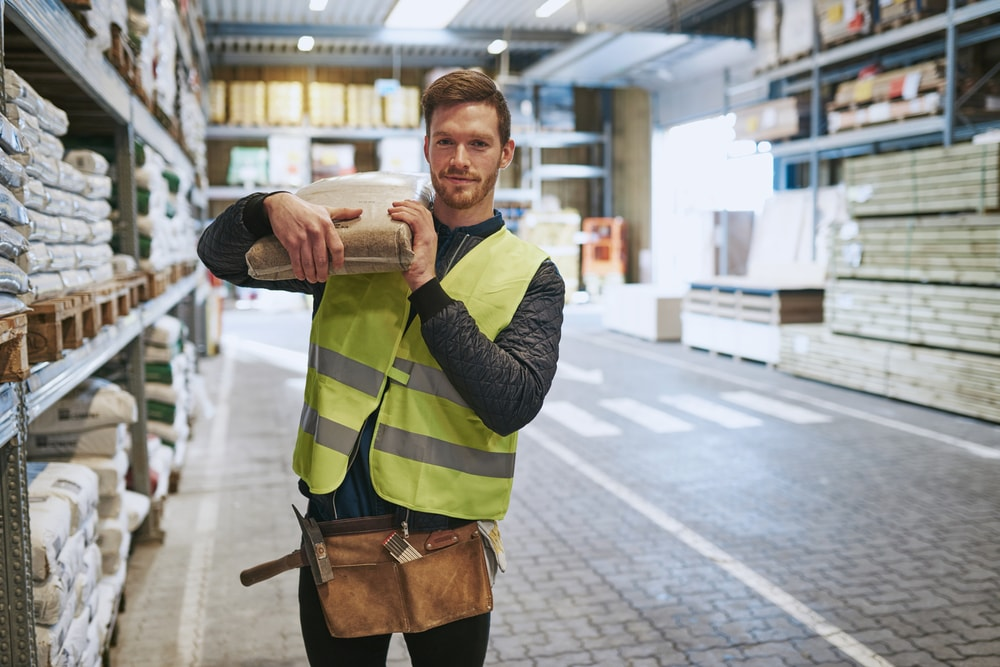 A young handyman working at a warehouse carrying a small parcel over his shoulders.