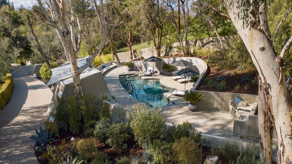 Outside, there's a swimming pool with multiple sitting lounges on the side. There's an outdoor kitchen as well. Images courtesy of Toptenrealestatedeals.com.