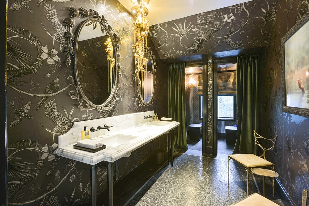 This bathroom has black patterned wallpaper to contrast the white two-sink vanity. On the far side is a couple of entryways to the toilet area. Image courtesy of Toptenrealestatedeals.com.