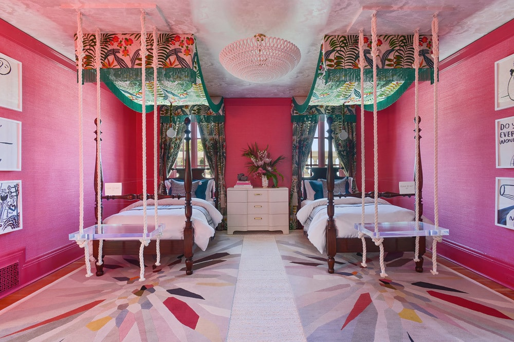 This eclectic and chic bedroom has a couple of wooden four-poster beds with green patterned curtains above that stand out against the pink walls and ceiling. Image courtesy of Toptenrealestatedeals.com.