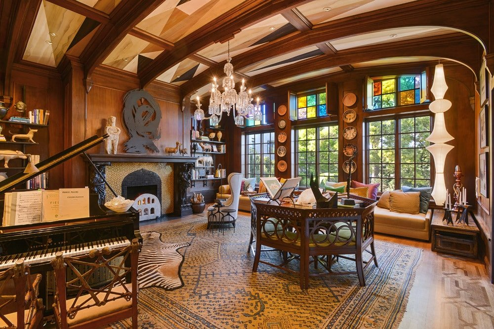 The spacious den has dark wooden tones to its exposed beams and walls to match the mantle of the large fireplace at the far side. These are then complemented by large arched windows with stained glass panels at the top. Image courtesy of Toptenrealestatedeals.com.