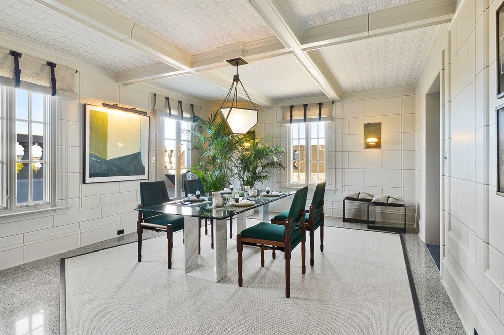 This is a simpler and more intimate dining room with white walls, floor and ceiling with exposed beams. These make the green cushions of the chairs stand out. Image courtesy of Toptenrealestatedeals.com.