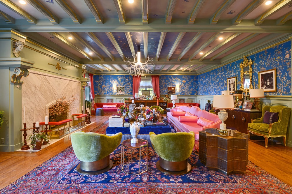 This large family room dominated by reds and blues with intricate patterns on the floor, walls and ceiling that has exposed beams. Image courtesy of Toptenrealestatedeals.com.