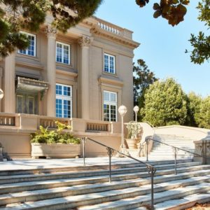 This is the front view of the house. You can see here the sandy beige exterior walls of the house complemented by large windows and tall pillars of the same tone as the walls. These are then augmented by the landscaping filled with trees and shrubs. Image courtesy of Toptenrealestatedeals.com.