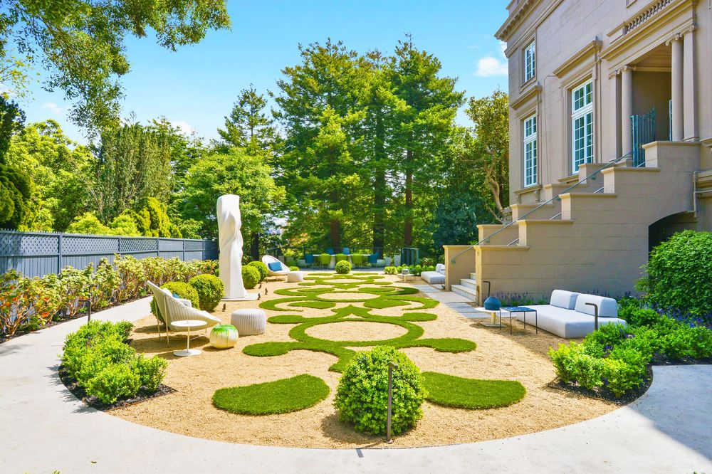 This is a view of the garden just below the concrete steps at the side of the house. Here you can see the patterned landscaping done to the grass lawn and its shrubs. Image courtesy of Toptenrealestatedeals.com.
