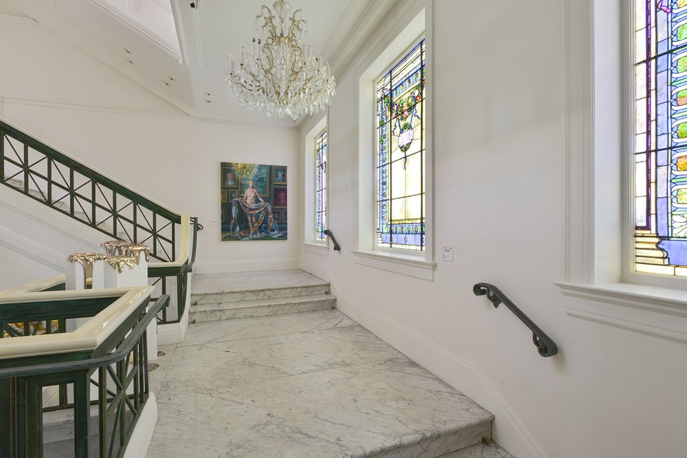 This is a closer look at the second floor landing. Here you can see the white marble floor that matches with the light tones of the walls adorned with stained glass windows. Image courtesy of Toptenrealestatedeals.com.