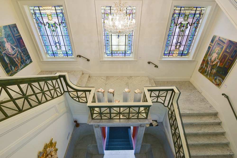This is a view of the second floor landing from the vantage of the third floor. This angle features three stained glass windows that bring color to the white walls. Image courtesy of Toptenrealestatedeals.com.