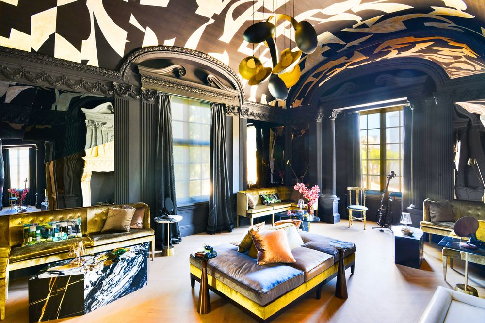 The library has a tall cove ceiling adorned with black and white patterns to match with the black walls and black curtains. This spacious room has various sets of sitting areas and reading nooks. Image courtesy of Toptenrealestatedeals.com.