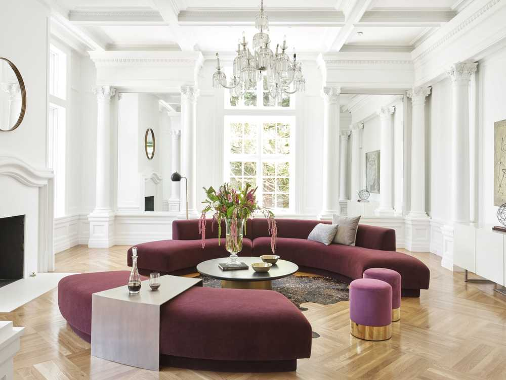 This formal living room has a tall white coffered ceiling to match the white walls adorned with white pillars. These make the maroon velvet sofa set stand out. Image courtesy of Toptenrealestatedeals.com.