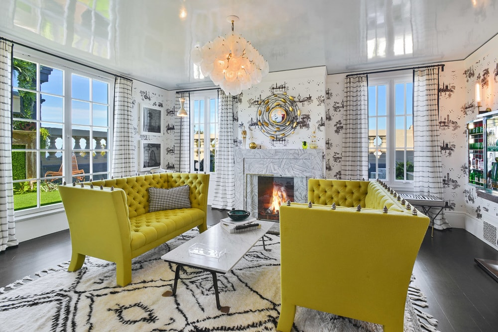This living room has a pair of lime green sofas flanking a long and narrow white coffee table across from the fireplace. Image courtesy of Toptenrealestatedeals.com.