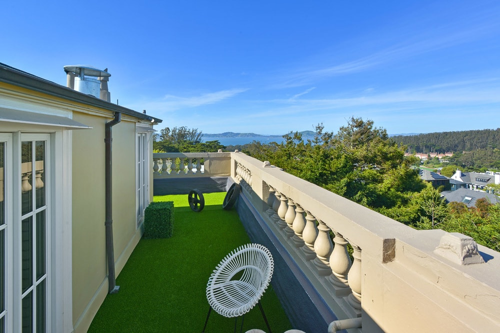 This is the other side of the rooftop patio fitted with an outdoor chair that stands out against the grass carpet. Image courtesy of Toptenrealestatedeals.com.