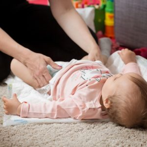 A mother changing the diaper of her baby on the carpet.