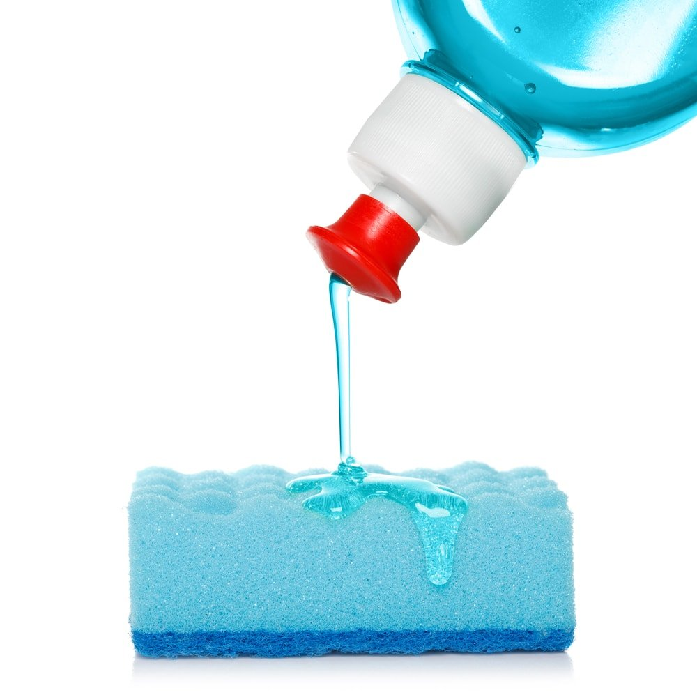 A bottle of dish detergent being poured onto a sponge.