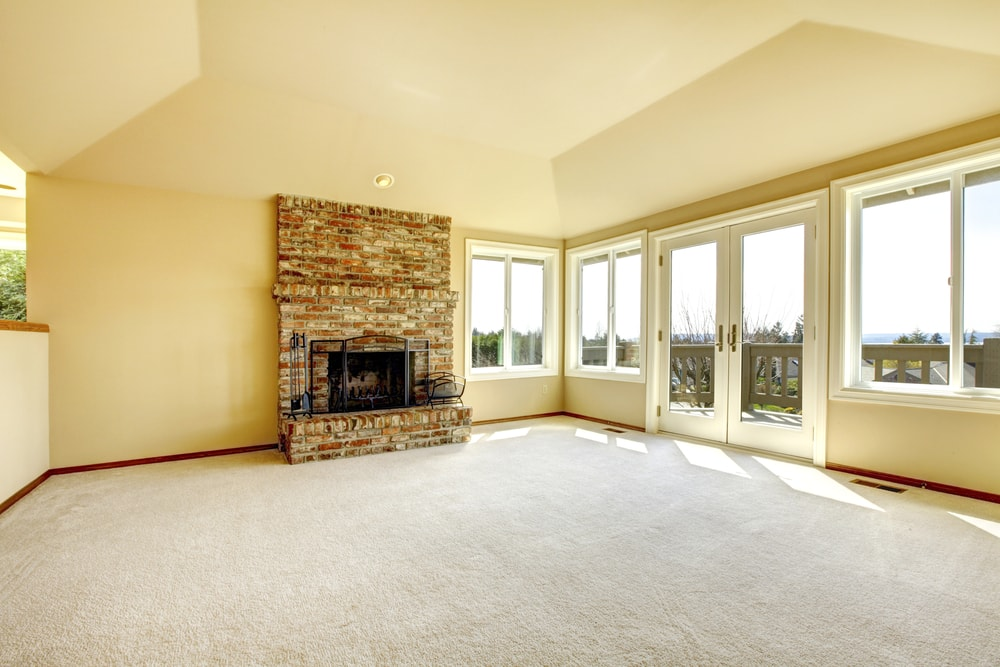 An empty living room with high vaulted ceiling, gray carpeting and a stone fireplace.